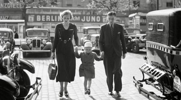 In this photo from the late 1920s or early 1930s provided by the International Center of Photography, a German family walks between taxicabs in front of the Ufa-Palast movie theater in Berlin. (Source: AP)