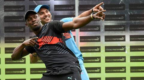 Olympic Gold medalist sprinter Usain Bolt strikes his trademark pose with Yuvraj Singh during a friendly cricket match in Bangalore. (Source: PTI)