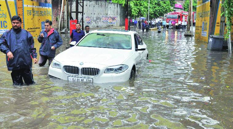 Fire brigade personnel drag a car  stuck in the waterlogged Mithakhali underbridge in Ahmedabad. (Source: Express photo by Javed Raja)