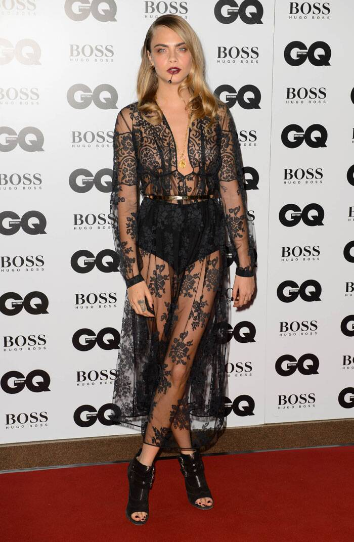 Supermodel Cara Delevingne was edgy and sensuous in a black lace sheer dress by Burberry, accessorised with a cocktail stick dangling from her lips. (Source: AP)