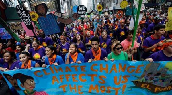Young people carry banners and signs as they demonstrate in a climate change march Sunday, Sept. 21, 2014, in New York. (Source: AP)