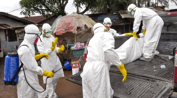 Health workers carry load the body of a woman that they suspect died from the Ebola virus, onto a truck in front of a makeshift shop in an area known as Clara Town in Monrovia, Liberia. (Source: AP)