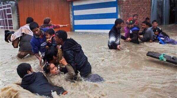 Kashmiri residents wade through floodwaters in Srinagar on Thursday. At least 100 villages across the Kashmir valley were flooded by overflowing lakes and rivers. (AP Photo)