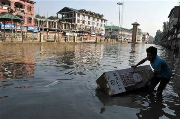A shopkeeper tries to pull a submerged clock from the flooded road of the business hub of Lal Chowk in Srinagar on Friday. (Source: PTI)