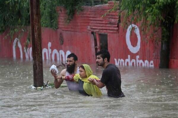 Kashmiri men help a woman move to a safer place after her neighborhood was flooded in Srinagar on Thursday. (AP photo)