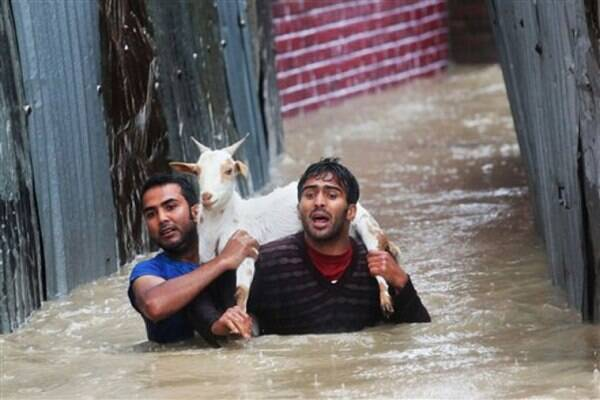 Srinagar residents carrying a goat wade through floodwaters in Srinagar on Thursday. (AP Photo)