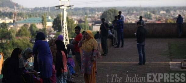 Residents trying out for mobile signals from high grounds in Srinagar. (Source: Express Photo by Tashi Tobgyal)