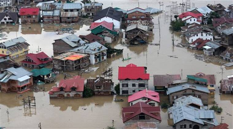 Flood-affected people row boats past partially submerged buildings in floodwaters in Srinagar. (Source: AP)