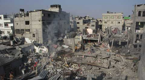 FILE - In this Saturday, Aug. 2, 2014 file photo, Palestinians stand on the rubble of houses destroyed in an Israeli strike in Rafah, southern Gaza Strip. (Source: AP)
