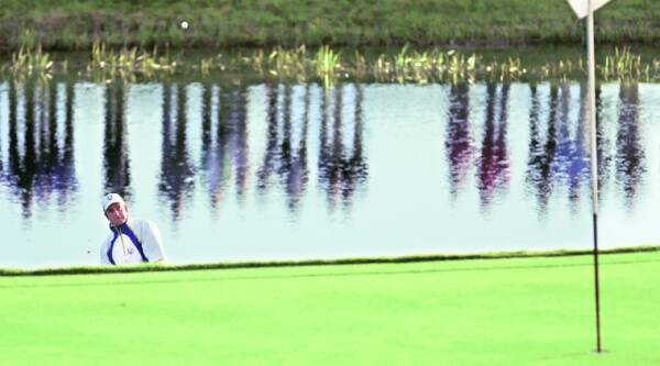 Henrik Stenson stands in the lake to play a shot onto the 2nd green on the second day.  Source: REUTERS