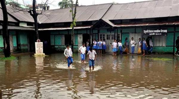 School students wade through flood water at a school after heavy showers in Guwahati on Friday. (Source: PTI)