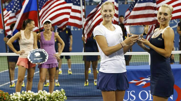 Ekaterina Makarova and Elena Vesnina (R), both from Russia, hold their trophy after defeating Martina Hingis and Flavia Pennetta (rear, L) in women's doubles at U.S. Open. (Source: Reuters)
