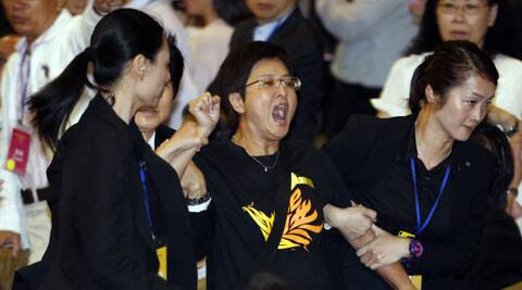 Pro-democracy lawmaker Helena Wong Pik-wan, center, is taken away by security guards after a protest against Li Fei, deputy secretary general of the National People's Congress' Standing Committee, during a briefing session in Hong Kong Monday, Sept. 1, 2014. (Source: AP)