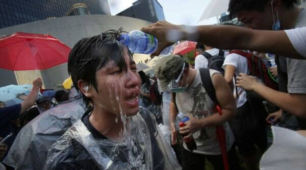 A student protester is overcome by pepper spray from riot police as thousands of protesters surround the government headquarters in Hong Kong Sunday, Sept. 28, 2014. (Source: AP)