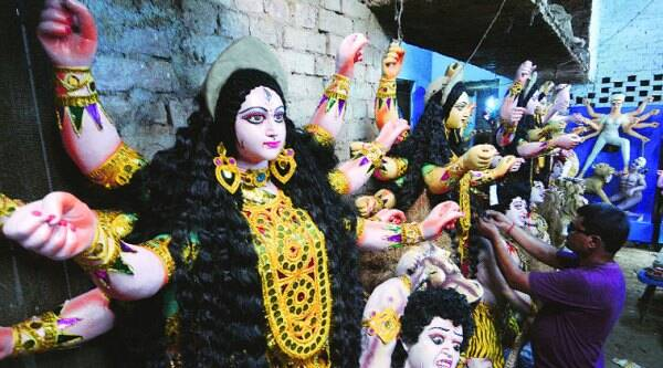 An artist gives finishing touches to idols of Goddess Durga, in Lucknow Sunday.