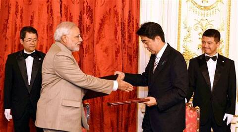 Prime Minister Narendra Modi and Japan's Prime Minister Shinzo Abe exchange files after signing an agreement at Akasaka Palace in Tokyo on Monday. (PTI Photo)