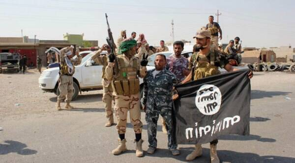 Shiite militiamen hold the flag of the Islamic State group they captured, during an operation outside Amirli, some 105 miles (170 kilometers) north of Baghdad, Iraq. Under the shadow of the Islamic State group threat, governments from France to Indonesia are moving aggressively to block would-be jihadis from taking their fight to Syria and Iraq. (Source: AP)