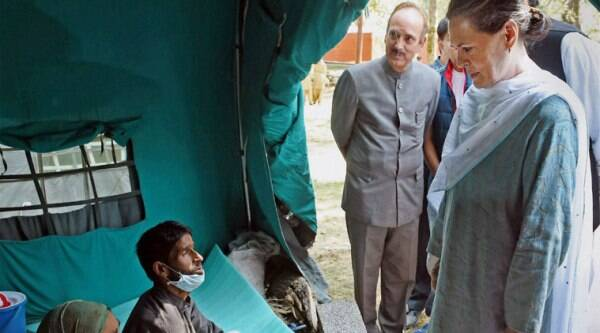 Sonia Gandhi and senior leader Ghulam Nabi Azad meeting with a flood affected family at Dehruna village of Anantnag district of South Kashmir on Monday. (Source: PTI)