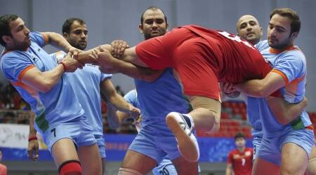 Thailand's Phuwanai Wannasaen, in red jersey, is caught by India team, in blue jersey, during the men's team kabbadi preliminary match (Source: AP)