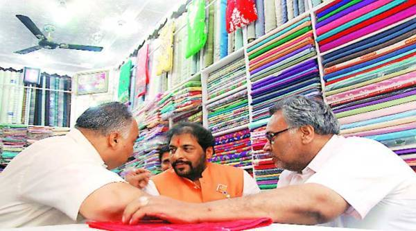 Gopal Kanda in conversation with voters at a saree shop in Sirsa city during his campaign. ( Source: Express photo by Gajendra yadav )