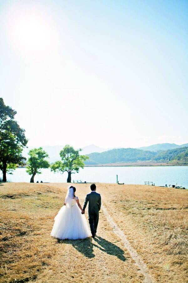 A bride and her groom walk towards the lake