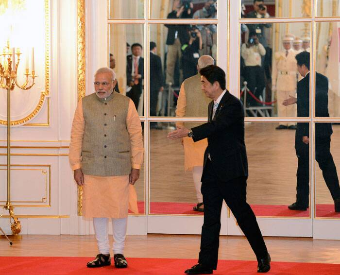 Prime Minister Narendra Modi, left, is shown the way by Japanese Prime Minister Shinzo Abe together during a welcome ceremony at Akasaka State Guesthouse in Tokyo. (Source: AP)