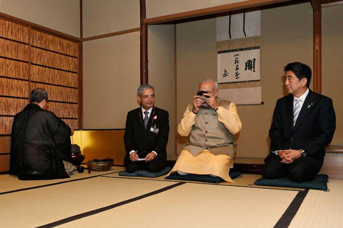 Prime Minister Narendra Modi, second right, drinks a bowl of rea as Japanese Prime Minister Shinzo Abe, right, looks on during a tea ceremony at a tea hut of the Omotesenke, one of the main schools of Japanese tea ceremony, in Tokyo. (Source: AP)