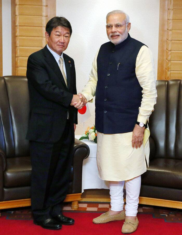 Japanese Minister of Economy, Trade and Industry Toshimitsu Motegi, left, shakes hands with Indian Prime Minister Narendra Modi prior to their meeting in Tokyo Monday. (Source: AP)