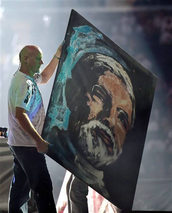 A painter carries Prime Minister Narendra Modi's portrait after making it in front of the crowd during a reception organised by the Indian American Community Foundation at Madison Square Garden in New York on Sunday. (Source: PTI)
