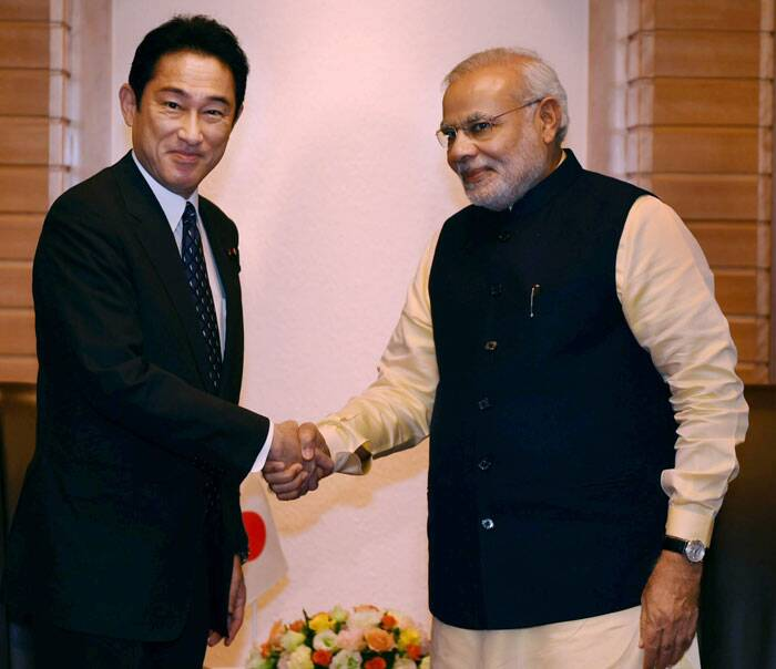Prime Minister Narendra Modi shakes hands with Japanese Minister of Foreign Affairs Fumio Kishida at a meeting in Tokyo on Monday. (Source: PTI)