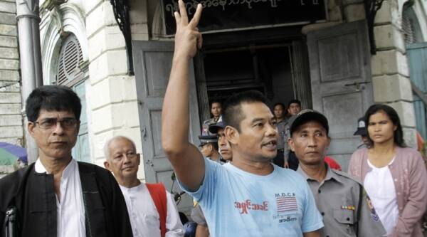 In this photo taken on Aug. 4, 2014, activist Htin Kyaw, right, shouts as he leaves a district court along with his lawyer Robert San Aung, left, after his trial in Yangon, Myanmar. (Source: AP)