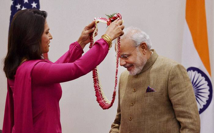 Gabbard, a 33-year-old US Democrat Congresswoman from Hawaii, called on the Prime Minister at his hotel. 	She presented to the Prime Minister a copy of Gita, which she had placed in her hand when she took oath while being sworn in to the US House of Representative. <br /><br /> Prime Minister Narendra Modi greeted with a garland by Member of House of Representatives Tulsi Gabbard during a meeting in New York on Sunday. (Source: PTI)
