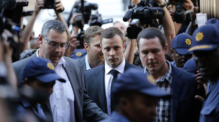 South African Olympic and Paralympic track star Oscar Pistorius (C) arrives for the verdict in his murder trial at the High Court in Pretoria (Source: Reuters)
