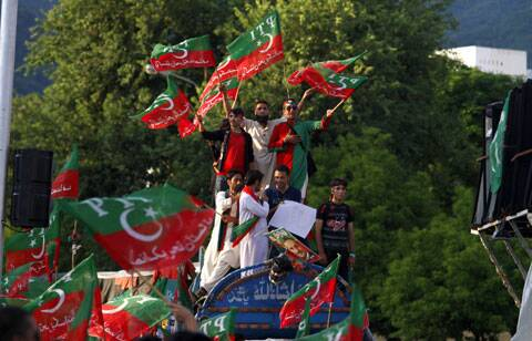 upporters of Pakistan's cricketer-turned-politician Imran Khan wave party flags as they chant slogans during a protest near Prime Minister's home in Islamabad. (Source: AP)