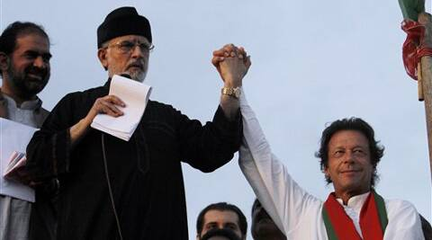 Pakistan's fiery cleric Tahir-ul-Qadri, second left, and cricketer-turned-politician Imran Khan, right, jointly raise their hands for their supporters during a protest near Prime Minister's home in Islamabad. (Source: AP photo)