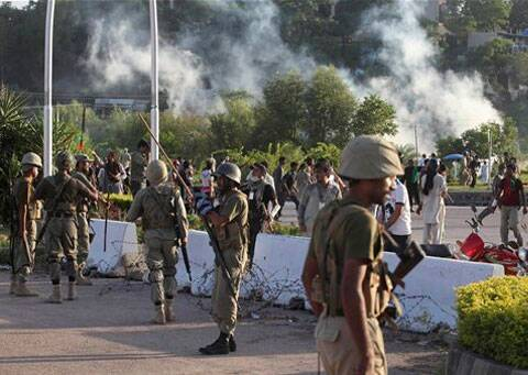Pakistani paramilitary troops stand guard during a clash between police and protesters in Islamabad. (Source: AP)