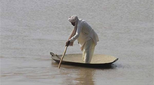 A Pakistani villager wades through floodwaters in district Shorkot near Jhang, Pakistan. (Source: AP)