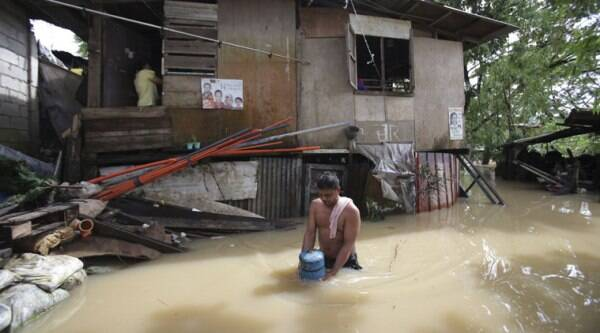 A Filipino wades through floodwaters as residents who earlier evacuated due to a swollen river return to their homes in suburban Quezon city, Philippines Monday, Sept. 15, 2014. (Source: AP)
