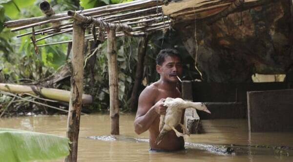 A Filipino holds a duck outside his house as a swollen river slowly recedes in suburban Quezon city, Philippines Monday, Sept. 15, 2014. (Source: AP)