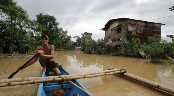 A Filipino boatman passes by a flooded village sitting beside a swollen river as it slowly recedes in suburban Quezon city, Philippines on Monday, Sept. 15, 2014. (Source: AP)