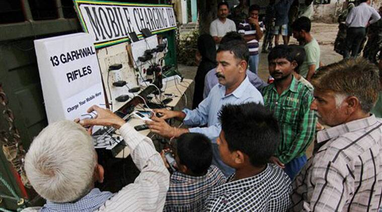 (Flood affected people charging mobile phones at an Army relief camp in Jammu on Friday. (Source: PTI)