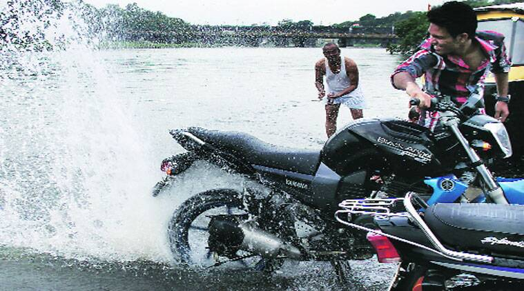 A two-wheeler owner splashes water that overflowed river banks on Wednesday. (Source: Express photo by Arul Horizon)