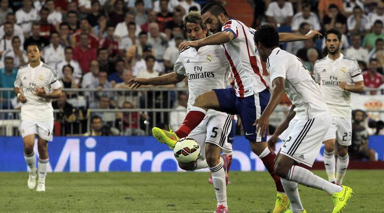 Arda Turan battles for the ball with Fabio Coentrao. (Source: AP)