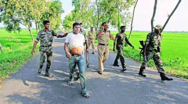 Police and RAF personnel arrest a TMC activist for allegedly throwing crude bombs at a bus carrying BJP supporters in Birbhum, Friday. The BJP supporters were on their way to hold a protest at a police station. ( Source: PTI )