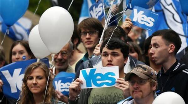 People hold up signs during a YES campaign rally in central Glasgow, Scotland, Wednesday. Source: AP photo