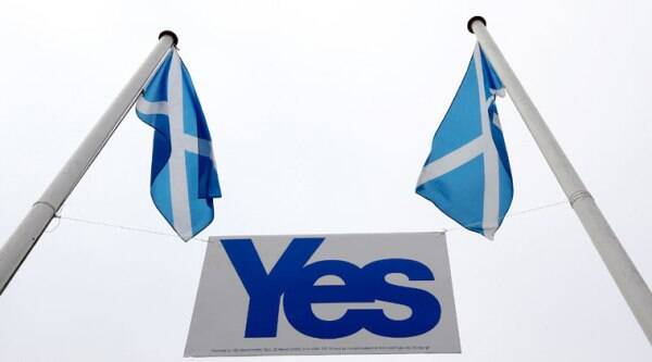 A pair of Saltire's fly above a Yes sign in Eyemouth, Scotland, Tueday, Sept. 16, 2014. (Source: AP)