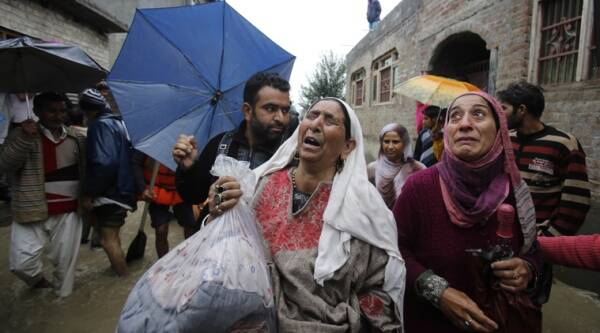 A Kashmiri woman cries as she is evacuated to a safer area, outside her home in Srinagar on Saturday. (AP Photo)