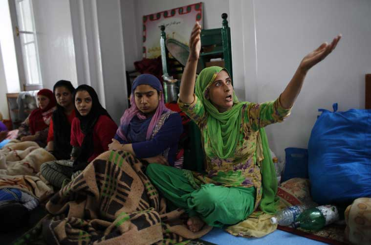 A Kashmiri woman narrates her tale of survival survival at a makeshift relief camp set up at a mosque in Srinagar, Indian-controlled Kashmir, Thursday, Sept. 11, 2014. (Source: AP photo)