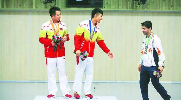 (From left) Silver medalist Cao Yifei and gold medalist Yang Haoran of China ask Abhinav Bindra to join them for a photo session during the Men's 10m Air Rifle victory ceremony. ( Source: AP )