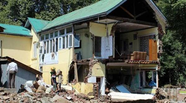 Flood hit victims salvage their belongings from their collapsed house at Saida Kadal in Srinagar on Friday. (Source: PTI)